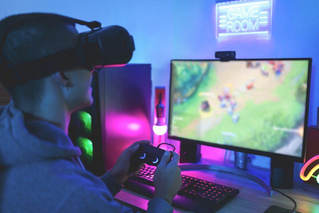 Gamer playing at computer game using joypad